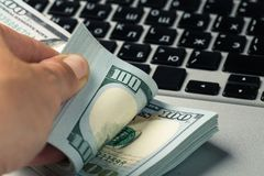 Hands holding dollar banknotes, laptop keyboard in background royalty free stock photos