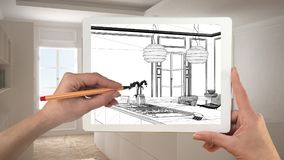 Hands holding and drawing on tablet showing modern kitchen CAD s. Ketch. Real finished minimalist white and wooden kitchen in the background, architecture stock images