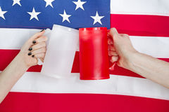 Hands holding drinking mugs with USA flag in background Stock Photos