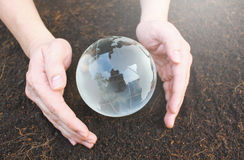 Hands holding earth made from glass Stock Photography