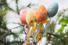 Hands holding Easter eggs on a stick, Stock Photo