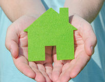Hands holding eco house icon concept as giving to the viewer Stock Photography