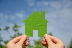 Hands holding eco house icon concept on the blue sky background. Hands holding green eco house icon concept on the blue sky background Stock Photography