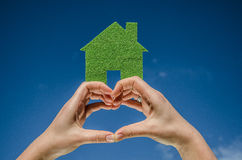 Hands holding eco house icon concept on the blue sky background in a shape of a heart Stock Photo