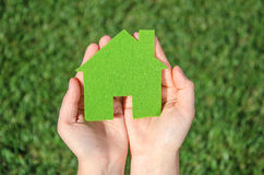 Hands holding eco house icon concept on the green grass background. On a sunny weather Royalty Free Stock Photos