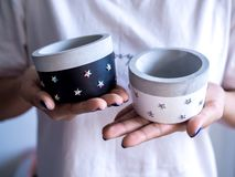 Hands holding empty black and white modern round concrete planters. Painted concrete pots for home decoration. Hands holding empty black and white modern round royalty free stock images