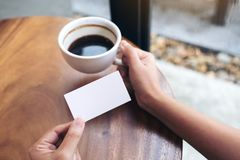 Hands holding an empty business card with coffee cup stock photo