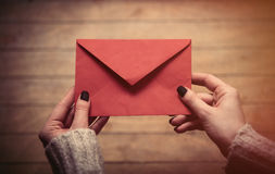 Hands holding envelope. Beautiful woman hands holding big red envelope on the wonderful brown wooden background Stock Images