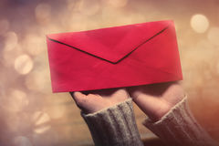Hands holding envelope. Beautiful woman hands holding big red envelope on the wonderful brown wooden background Royalty Free Stock Photos