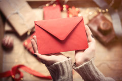 Hands holding envelope. Beautiful woman hands holding big red envelope on the wonderful  decoration background Royalty Free Stock Images