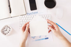 Hands holding envelope over desktop. Hands holding small blank envelope over office desktop with smartphone, clock, business report and other items. Topview Royalty Free Stock Photos