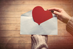 Hands holding envelope and toy. Beautiful woman hands holding big red envelope and putting heart shaped toy inside it on the wonderful brown wooden background Royalty Free Stock Photos