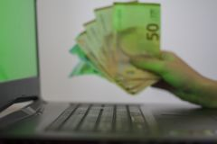 Hands holding euro money and using laptop with green screen