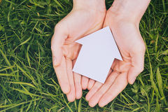 Hands Holding Family House on Grass Stock Photos