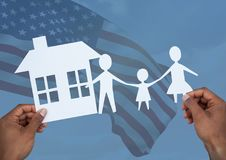 Hands holding a family and a house on paper against american flag. Digital composite of hands holding a family and a house on paper against american flag Stock Images