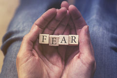 Hands holding Fear message. Formed with wooden blocks Stock Photo