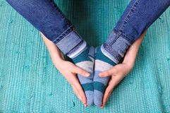 Hands Holding Feet. A pair of hands holding a pair of feet in socks Royalty Free Stock Image