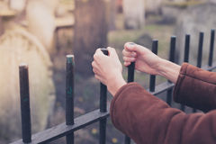 Hands holding fence at graveyard Stock Image