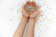 Hands holding festive confetti. White background. Small circles stock photos