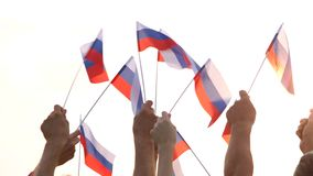 Hands holding flags of Russian Federation. Peaceful Russian patriots waving flags outdoors. People, freedom and patriotism stock video