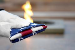 Hands holding folded American flag on Eternal flame. Background stock image