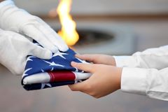 Hands holding folded American flag on Eternal flame. Background stock images