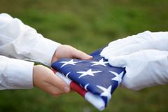 Hands holding folded American flag. On green grass background stock images