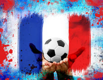 Hands holding football on France's flag colored background Royalty Free Stock Photo