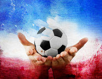 Hands holding football on France's flag colored background Royalty Free Stock Photos