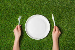 Hands holding fork and knife with plate on grass Stock Image