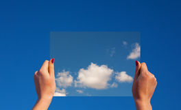 Hands holding a frame with clouds Royalty Free Stock Photos