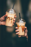 Hands holding frappes. Two hands holding frappe drinks in take-out plastic cups Royalty Free Stock Photography