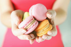 Hands holding french macarons Stock Images