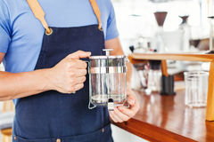 Hands holding french press coffee pot Stock Image