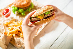 Hands holding fresh delicious burger with french fries, sauce on the wooden table. Top view. Flat lay Royalty Free Stock Photos