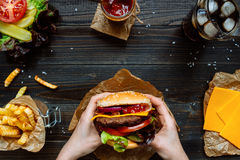 Hands holding fresh delicious burgers with french fries, sauce and beer on the wooden table top view.  Royalty Free Stock Image