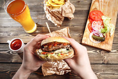 Hands holding fresh delicious burgers with french fries, sauce and beer on the wooden table top view. stock image