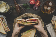 Hands holding fresh delicious club sandwich, sauces and drink on the wooden dark table, top view Stock Photography