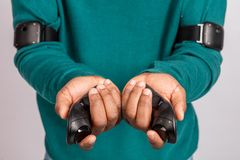 Hands holding gamepads from virtual reality headset. VR technology gadget. Hands of dark- skinned man holding gamepads from virtual reality headset. Grey stock images