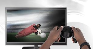 Hands holding gaming controller  with soccer player goalie on television. Digital composite of Hands holding gaming controller  with soccer player goalie on Royalty Free Stock Photos