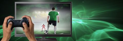 Hands holding gaming controller with soccer player on television stock photo