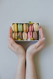 Hands holding gift box with delicious macaroons on the light blue background, top view Stock Images