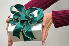 Hands Holding Gift with Green Bow. Hands are holding a gift of a white box and deep green wire edged ribbon bow with metallic gold edges Royalty Free Stock Images