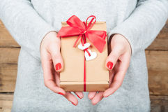 Hands holding gift in kraft box on a wooden background. The conc