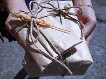 Hands holding gifts wrapped in old vintage brown paper and tied with rope Royalty Free Stock Image
