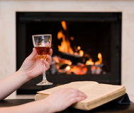 Hands holding glass of cognac and book by the fireplace Royalty Free Stock Photography