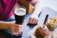 Hands holding glass of cold dark beer. Burgers with french fries on the table stock photos