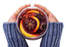 Hands holding a glass cup with mulled wine. Spices, orange, anise and cinnamon sticks on white background Royalty Free Stock Photos