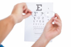 Hands holding glasses for eye test. On white background Royalty Free Stock Images