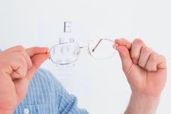 Hands holding glasses for eye test Stock Image